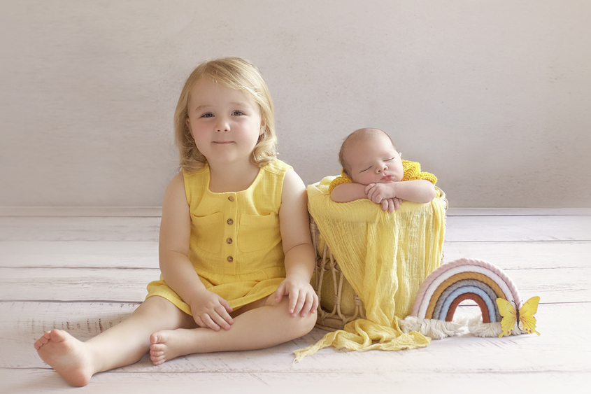 Newborn baby boy sleeping in cane basket wearing yellow knit romper with yellow wrap and sibling big sister sitting beside the basket wearing a yellow dress with macrame rainbow and yellow butterfly