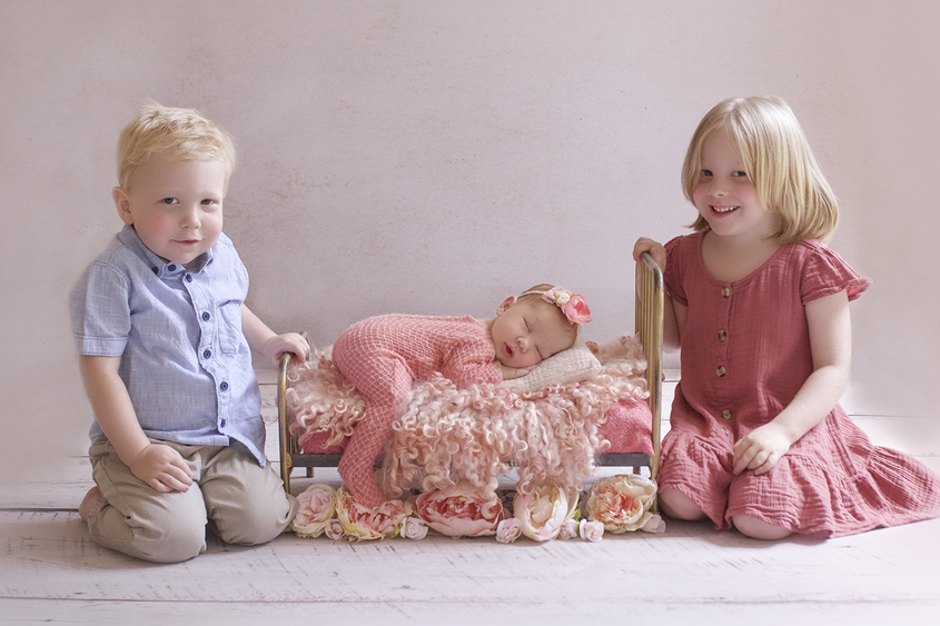 Newborn baby girl wearing coral romper sleeping on vintage iron bed with coral fur and flowers and flower tieback with sibling big sister and brother sitting beside her