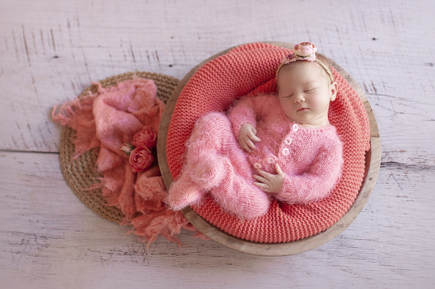 Newborn baby girl sleeping in round wooden bowl with coral blanket and wrap wearing coral knit romper and flower tieback with dried flowers and hessian circle layer