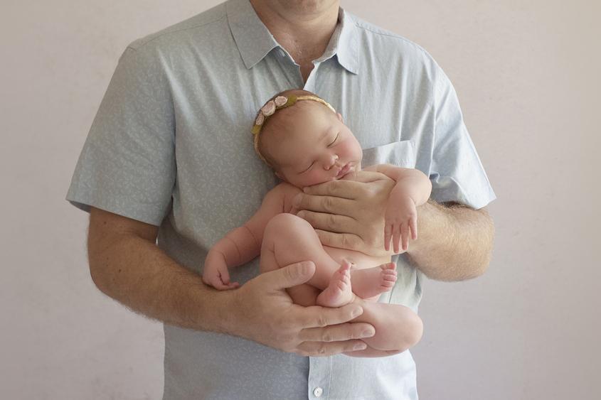 Newborn baby girl sleeping being held by father and wearing flower tieback