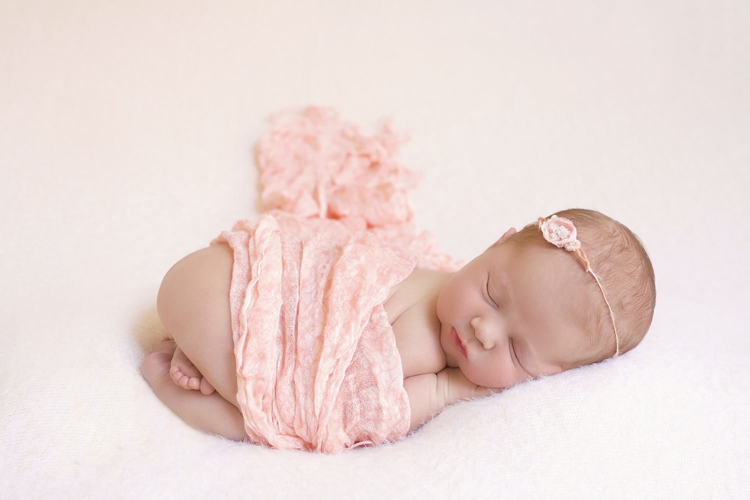 Newborn baby girl sleeping on cream blanket with peach wrap and tieback or knit bonnet