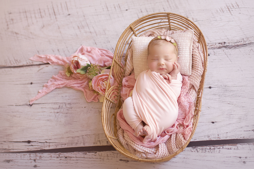Newborn baby girl wrapped in pink wrap sleeping in cane basket with pink blanket and layer with flowers and flower tieback on wooden floor