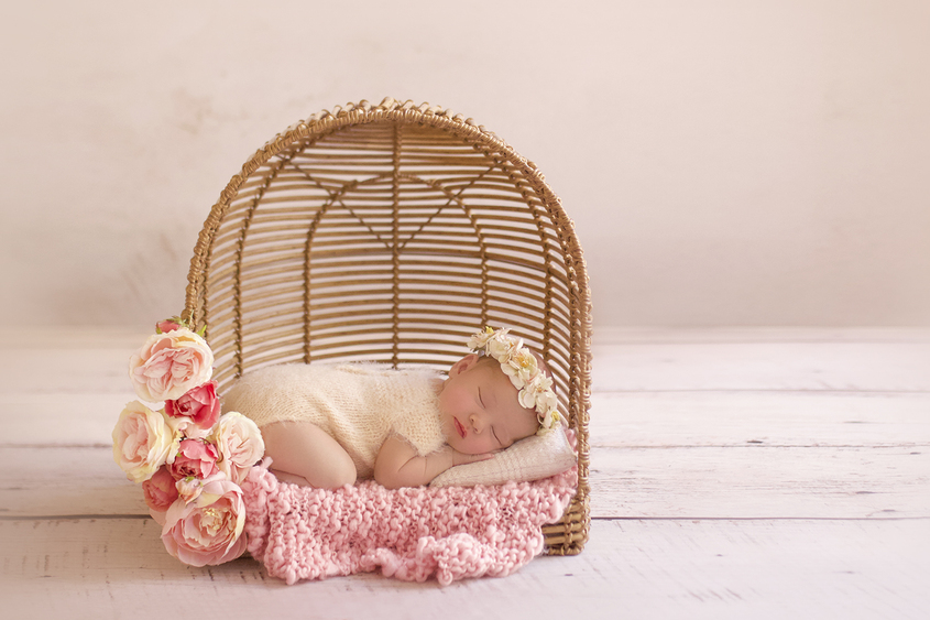 Newborn baby girl sleeping in cane basket with flowers and pink knit layer and cream pillow wearing cream knit romper and flower crown