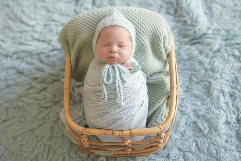 Newborn baby girl sleeping in cane basket wrapped in mint wrap on mint blanket on mint fur wearing mint knit bonnet